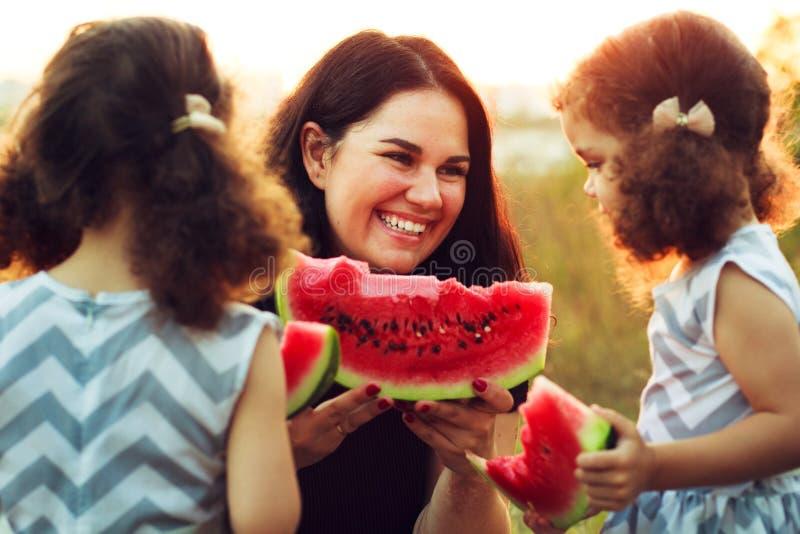 在野餐的逗人喜爱的愉快的家庭吃西瓜的 愉快的母亲和孩子孪生,温暖的夏天晚上光关闭,卷发姐妹 库存图片