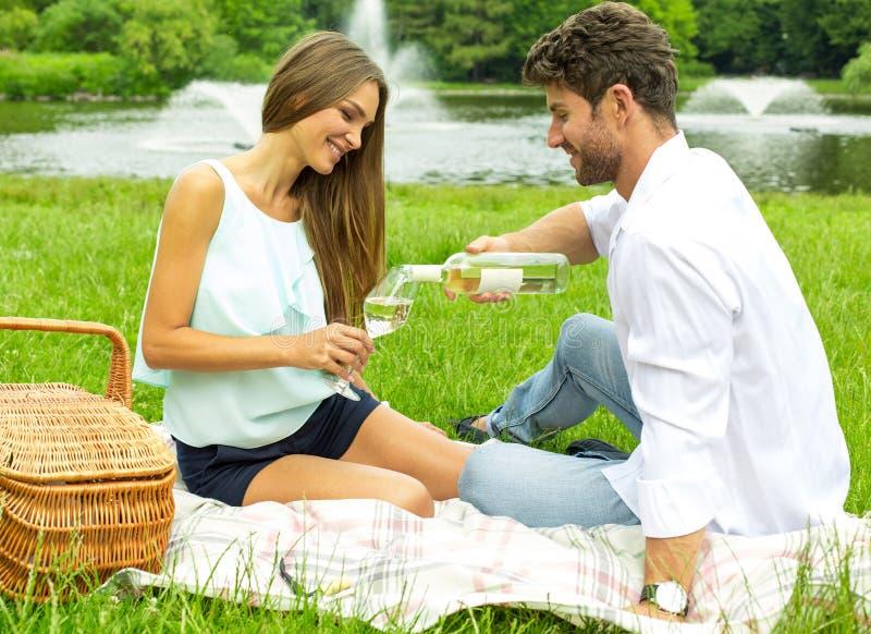 在野餐饮用的白葡萄酒的年轻夫妇 免版税库存照片
