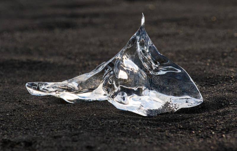 在金刚石海滩的令人惊讶的透明蓝色冰山片断与在冰河湖盐水湖,冰岛附近的黑沙子 冰产犊 ?? 库存照片