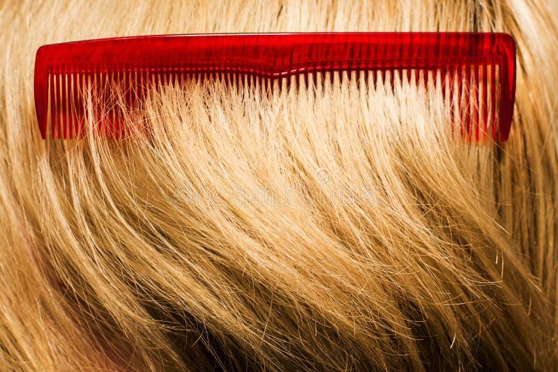 在金发的红色梳子 免版税库存图片
