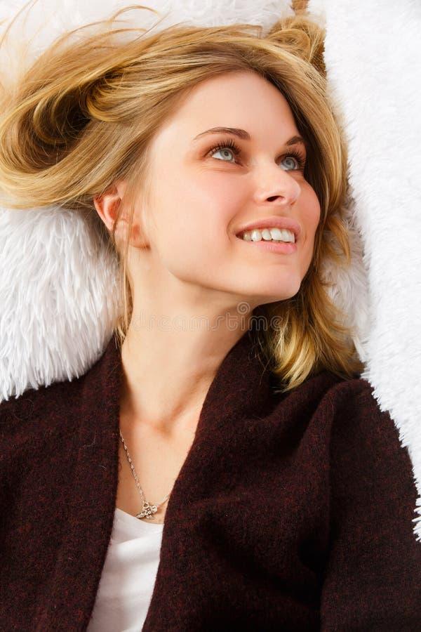在金发碧眼的女人顶部的图片说谎在白色毛皮盖子的毛线衣的 免版税库存照片
