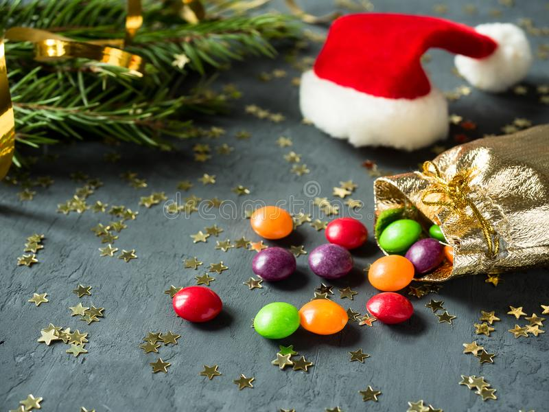 在金大袋的五颜六色的糖果在与星的灰色背景 圣诞树,佩带的圣诞老人 免版税库存照片