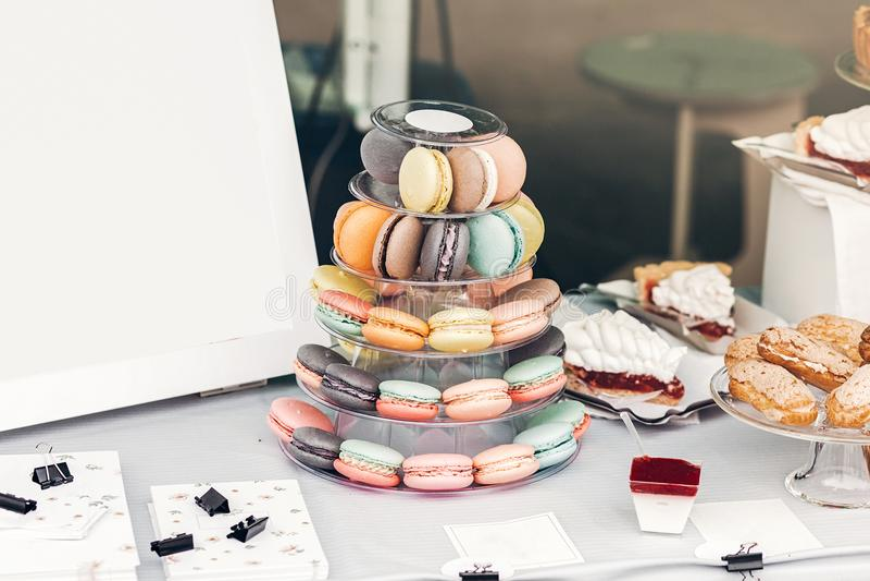 在金字塔立场和空的委员会的可口五颜六色的蛋白杏仁饼干 免版税库存照片
