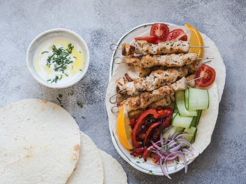 在金属串的烤鸡有在皮塔饼和希腊调味汁的新鲜蔬菜的在灰色背景的一个碗 希腊语 免版税库存图片