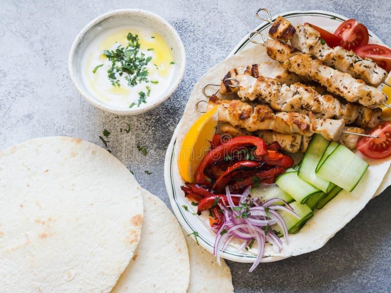 在金属串的烤鸡有在皮塔饼和希腊调味汁的新鲜蔬菜的在灰色背景的一个碗 希腊语 免版税库存照片