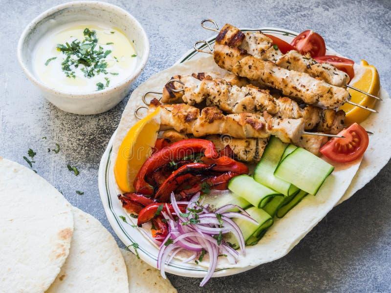 在金属串的烤鸡有在皮塔饼和希腊调味汁的新鲜蔬菜的在灰色背景的一个碗 希腊语 库存图片