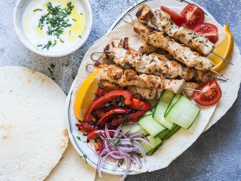 在金属串的烤鸡有在皮塔饼和希腊调味汁的新鲜蔬菜的在灰色背景的一个碗 希腊语 图库摄影