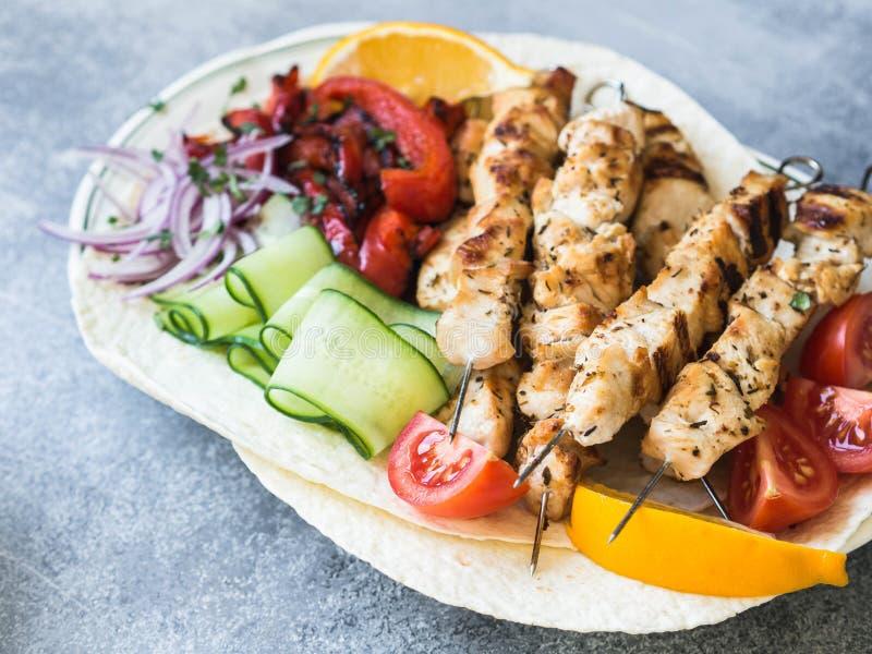 在金属串的烤鸡有在皮塔饼和希腊调味汁的新鲜蔬菜的在灰色背景的一个碗 希腊语 库存照片