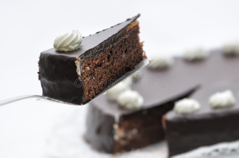 在金属匙子,在白色板材,法式蛋糕铺的生日蛋糕的Sacher奶油蛋糕,鞭打了在蛋糕,商店的,巧克力蛋糕摄影的奶油 图库摄影