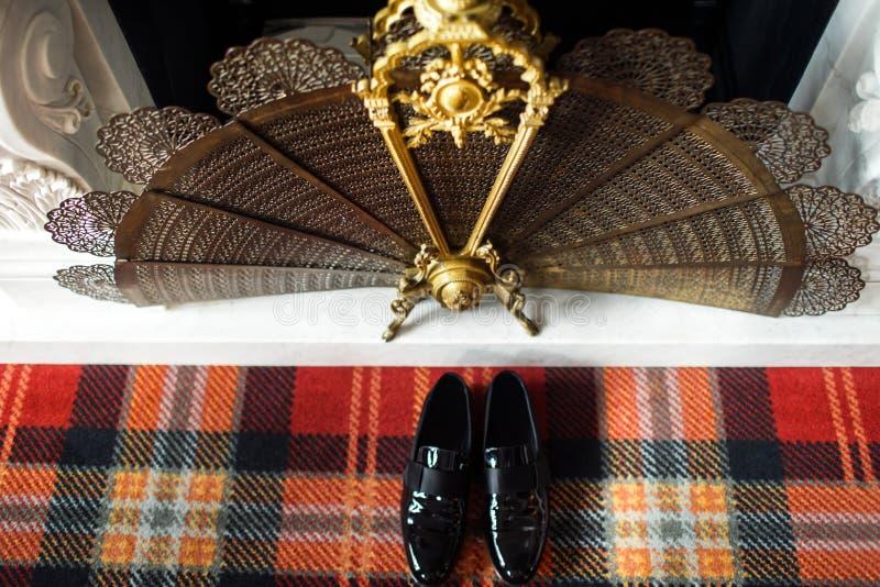 在金属壁炉附近的婚姻的黑鞋子关闭 免版税库存照片