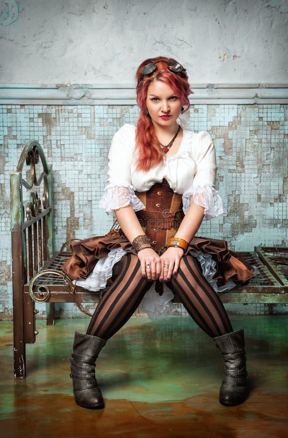 在金属床上的美丽的steampunk妇女 免版税库存图片