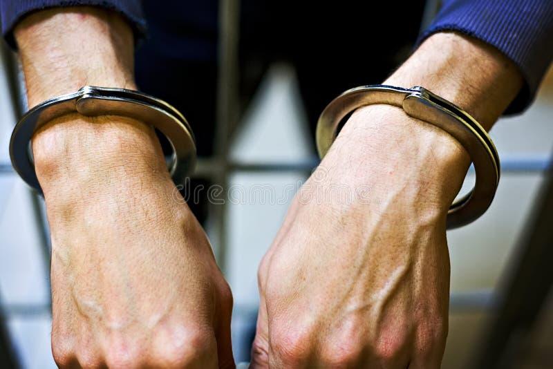 在金属手铐特写镜头的男性手 一个囚犯在监狱 处罚的概念对罪行的 库存图片