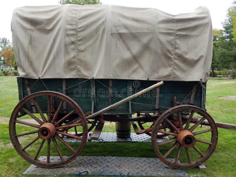 在金属板和草的绿色和棕色驿马车 库存图片