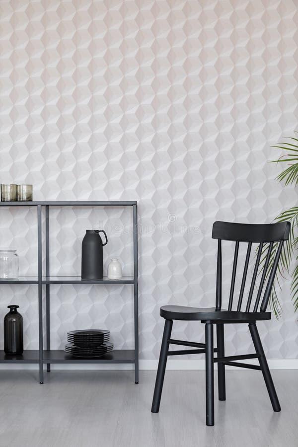 在金属架子旁边的黑木椅子与花瓶、板材和辅助部件在空的墙壁墙壁上有独特的墙纸的,真正的照片 向量例证