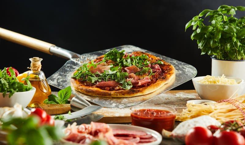 在金属桨的新近地被烘烤的比萨 免版税库存图片