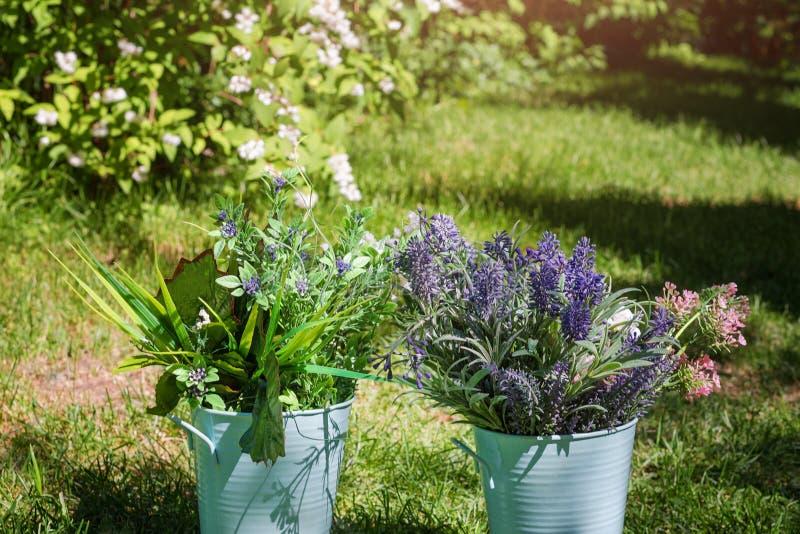 在金属桶的各种各样的鲜花安排在庭院里 欢乐事件的装饰花束 库存图片
