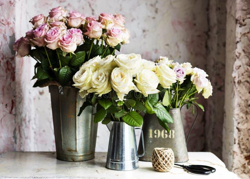 在金属桶的新桃红色和白玫瑰花的布置图片