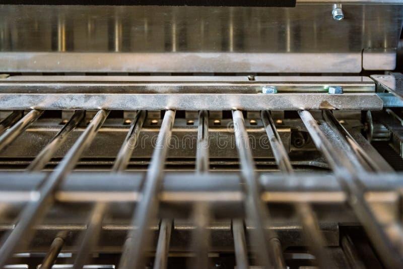 在金属棒新闻特写镜头里面的纸折叠的机器折叠单位 免版税库存图片