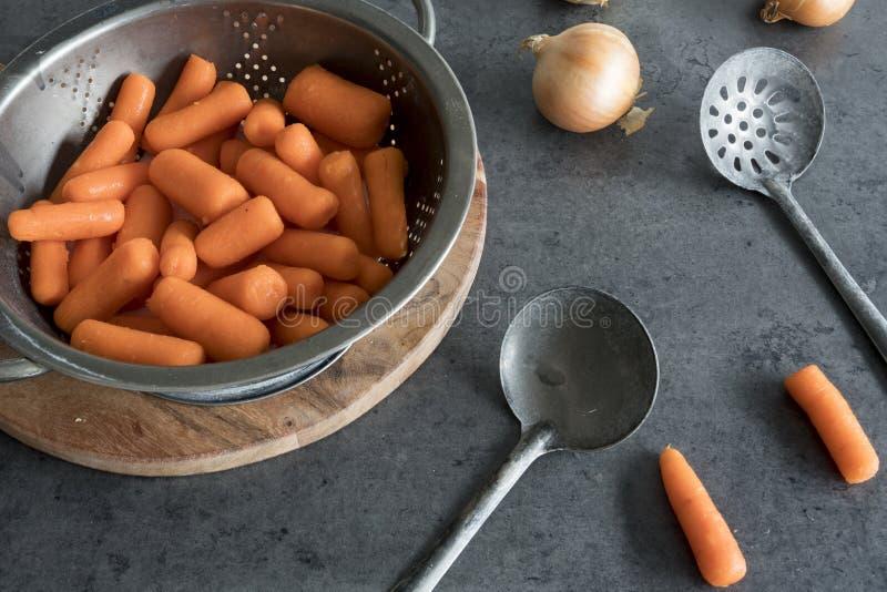 在金属滤锅的红萝卜有葡萄酒匙子的 库存照片