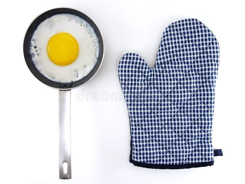 在金属煎锅的荷包蛋有银色不锈钢把柄和蓝色白色方格的样式在白色隔绝的烤箱手套的 免版税库存图片