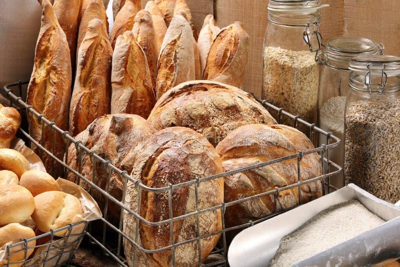 在金属篮子的新鲜面包在木背景的面包店 免版税库存图片