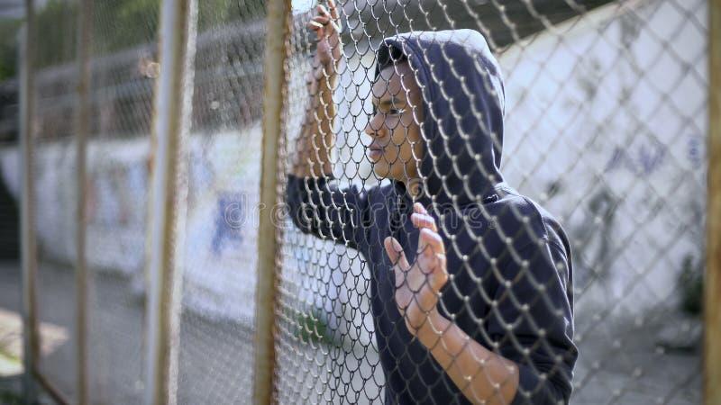 在金属篱芭后的美国黑人的男孩,犯罪在监狱,作梦关于自由 免版税库存图片