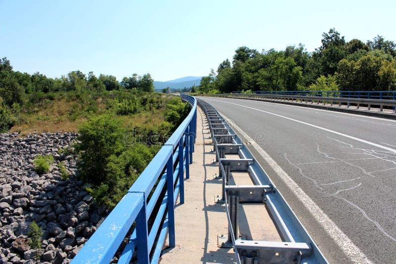 在金属篱芭和栏杆之间的狭窄的桥梁边路 免版税库存照片
