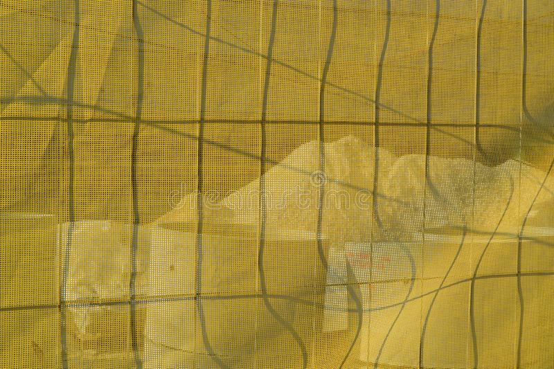在金属篱芭的黄色建筑滤网在一个建造场所附近在一个晴天 具体管子和堆石渣是visib 库存照片