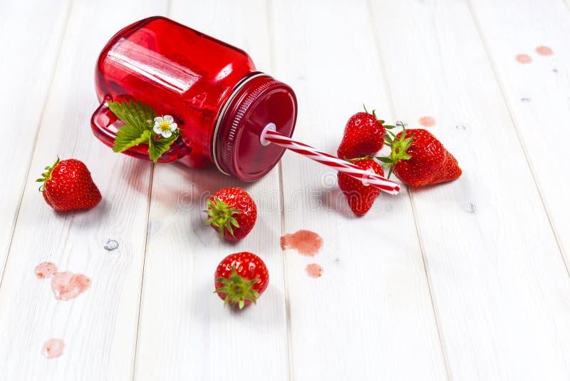 在金属螺盖玻璃瓶的草莓圆滑的人有秸杆的 免版税图库摄影