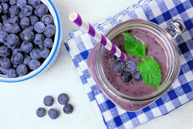 在金属螺盖玻璃瓶玻璃向下视图的蓝莓圆滑的人 库存图片