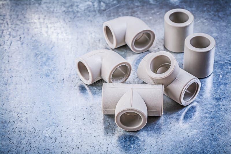 在金属表面建筑概念的塑料管子配件 免版税库存图片