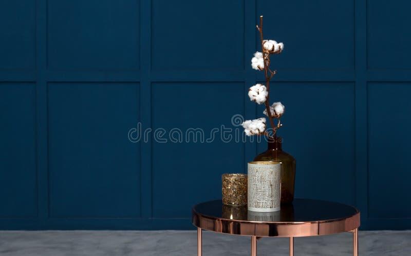 在金属铜旁边桌上的现代花瓶在有蓝色墙壁的屋子里 库存照片
