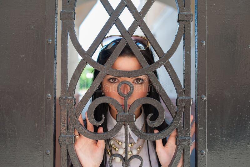 在金属门后的女孩 拿着金属篱芭 有长发的年轻迷人的十几岁的女孩有慈悲的恳求的眼睛的 库存图片