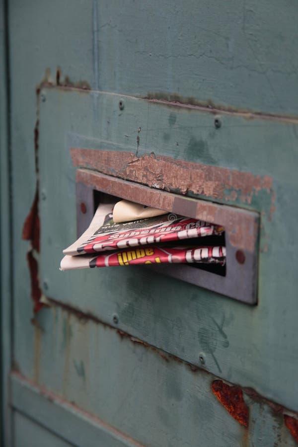 在金属门的老邮箱报纸 免版税库存照片