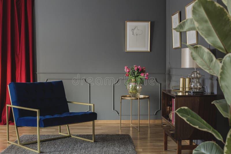 在金桌旁边的藏青色扶手椅子与在elega的桃红色花 库存照片