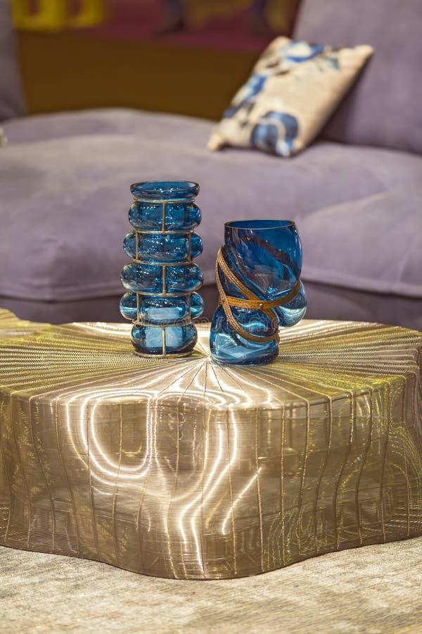 在金现代桌上的蓝色时兴的玻璃花瓶 时髦的内部艺术装饰 免版税库存照片