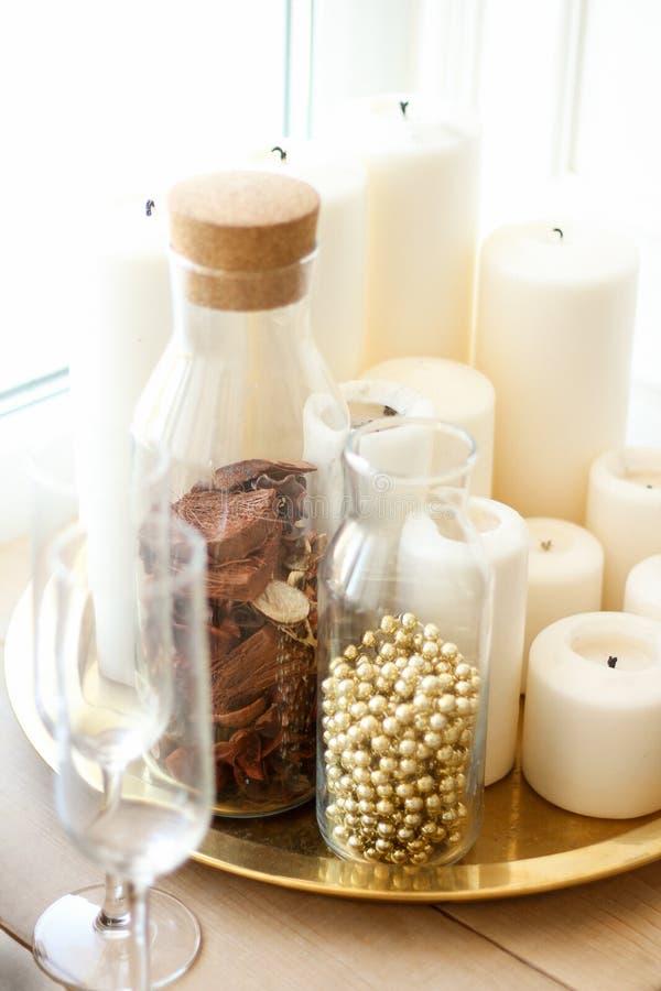 在金盘子上有蜡烛白色和透明瓶子,珍珠小珠和干燥花和玻璃附近的夫妇  免版税图库摄影