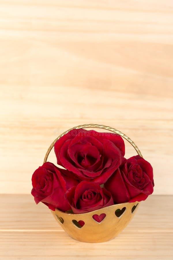 在金篮子,情人节,婚礼之日,木backg的红色玫瑰 免版税图库摄影