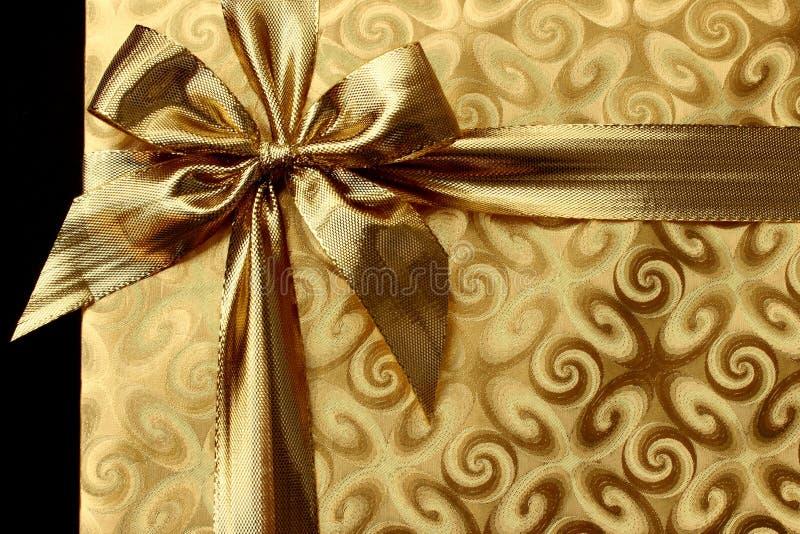 在金纸的圣诞节礼物与弓 背景 免版税库存图片