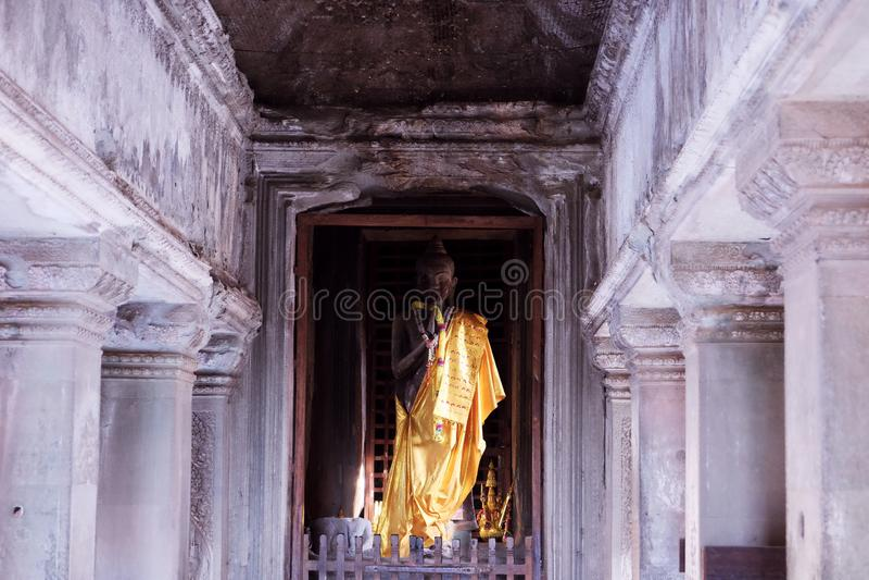在金衣裳穿戴的菩萨雕象 在吴哥寺庙的一个小佛教圣所  库存图片