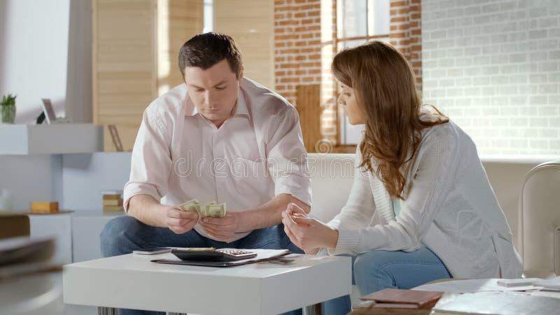 在金钱的丈夫和妻子翻倒,计数低家庭预算,失业 免版税库存图片