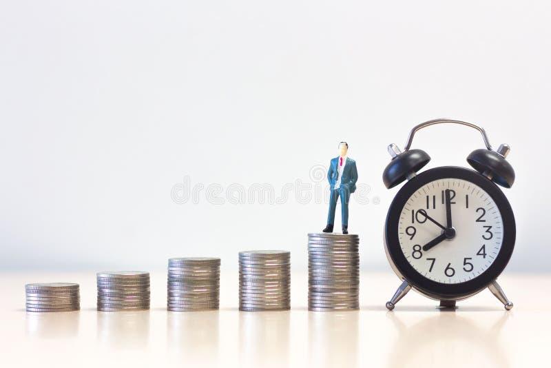 在金钱硬币堆的微型人商人身分与闹钟,财务可持续发展概念 免版税库存照片