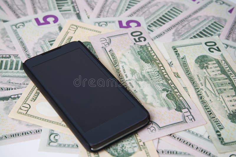 在金钱背景的电话  库存图片