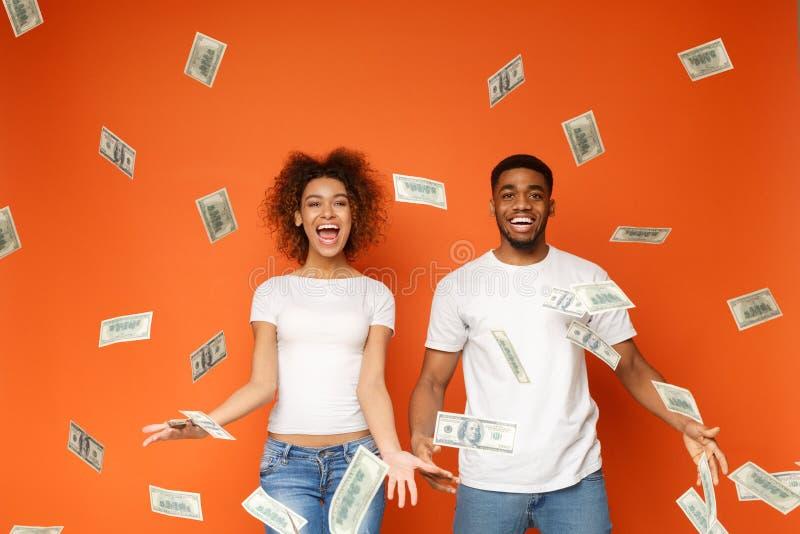 在金钱钞票阵雨下的年轻黑夫妇身分 库存图片