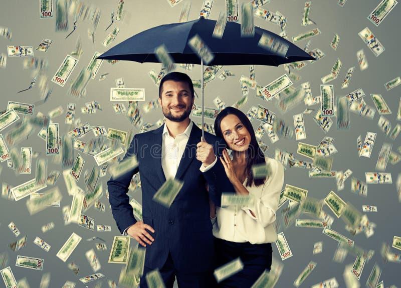 在金钱雨下的夫妇 库存图片