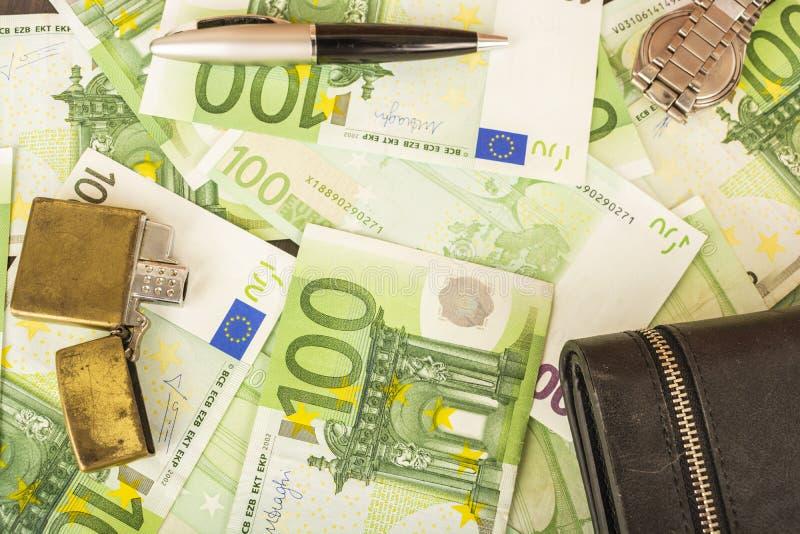 在金钱100欧洲笔记背景的更轻的钱包时钟笔  库存图片