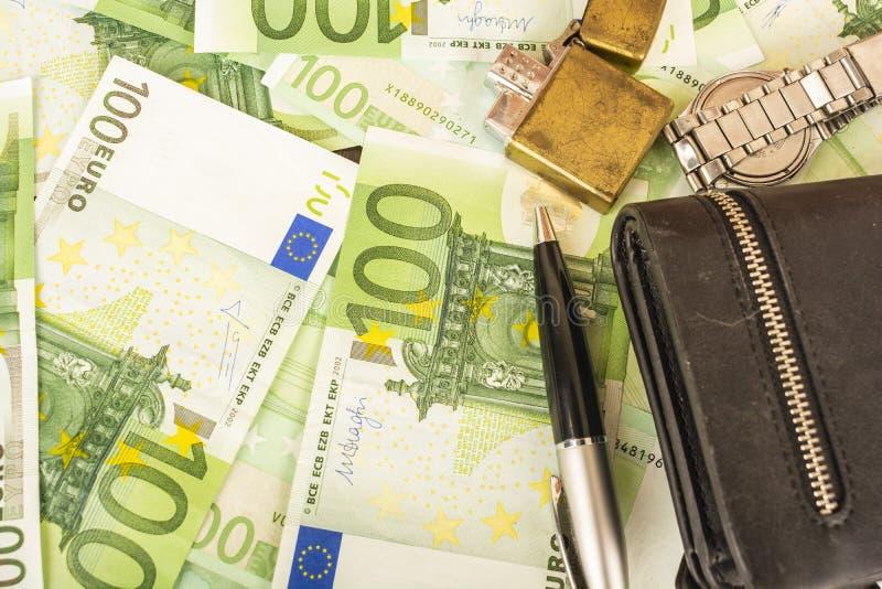 在金钱100欧洲笔记背景的更轻的钱包时钟笔  图库摄影