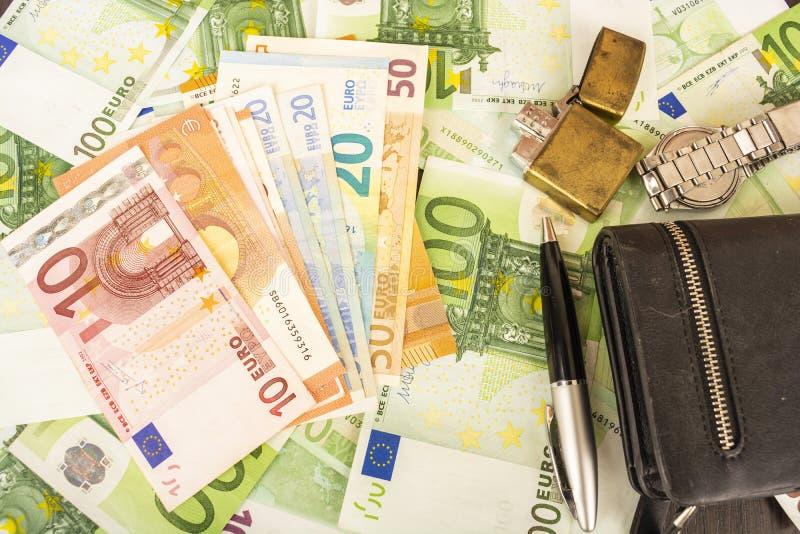 在金钱100欧洲笔记背景的更轻的钱包时钟笔  库存照片