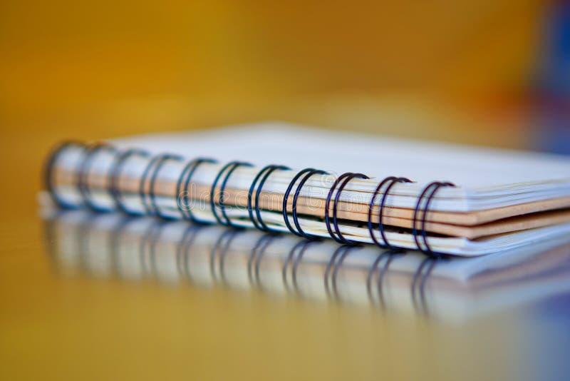 在金黄和蓝色背景的螺旋装订的笔记本与反射 r 研究和训练 免版税库存图片