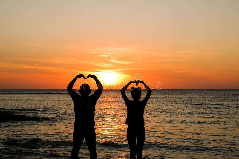 在金黄日落的夫妇在海滩 免版税库存照片